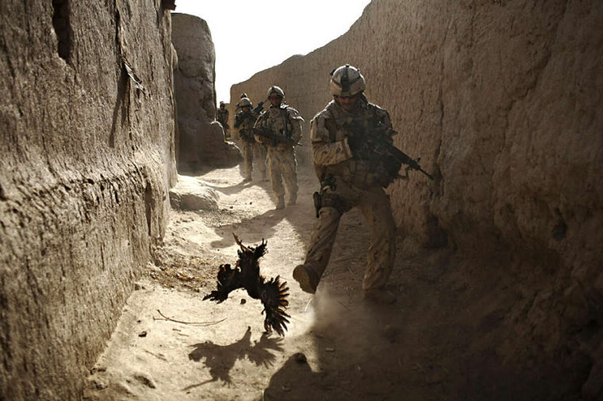 """FILE - In this Saturday, Sept. 11, 2010 file photo, a Canadian soldier with the 1st RCR Battle Group, The Royal Canadian Regiment, chases a chicken seconds before he and his unit were attacked by grenades shot over the wall during a patrol in Salavat, southwest of Kandahar, Afghanistan. Anja Niedringhaus, a courageous and immensely talented Associated Press photographer who has covered everything from sports to war, was killed while covering elections in Afghanistan on Friday April 4, 2014. Niedringhaus was in a car in eastern Afghanistan with AP reporter Kathy Gannon when, according to a freelancer who was with them, an Afghan policeman approached them, yelled """"Allahu Akbar"""" _ God is Great _ and opened fire on them in the back seat with his AK-47. Niedringhaus was killed instantly and Gannon was wounded. (AP Photo/Anja Niedringhaus, File)"""