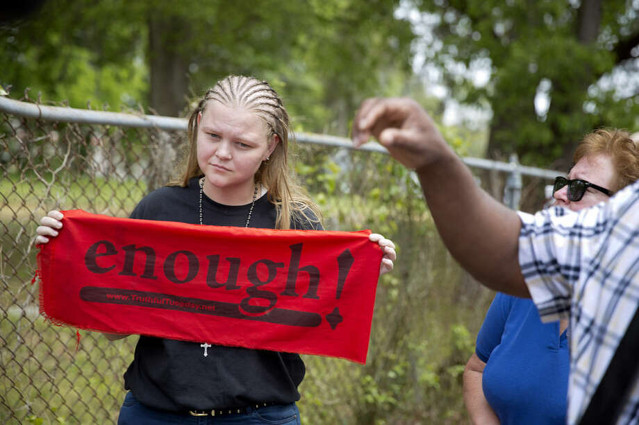 Asia Cromwell, of Charleston S.C., holds a banner while visiting the scene where Walter Scott was killed by a North Charleston police officer Saturday after a traffic stop in North Charleston, S.C., Friday, April 10, 2015. The officer, Michael Thomas Slager, has been fired and charged with murder. (AP Photo/David Goldman)