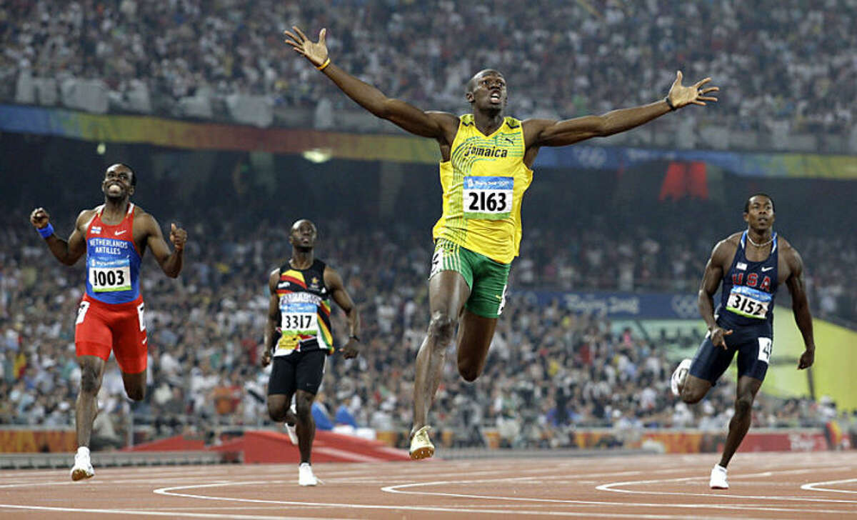 """FILE - In this Aug. 20, 2008 file photo, Jamaica's Usain Bolt crosses the finish line to win the gold in the men's 200-meter final at the Beijing 2008 Olympics in Beijing. Anja Niedringhaus, a courageous and immensely talented Associated Press photographer who has covered everything from sports to war, was killed while covering elections in Afghanistan on Friday April 4, 2014. Niedringhaus was in a car in eastern Afghanistan with AP reporter Kathy Gannon when, according to a freelancer who was with them, an Afghan policeman approached them, yelled """"Allahu Akbar"""" _ God is Great _ and opened fire on them in the back seat with his AK-47. Niedringhaus was killed instantly and Gannon was wounded. (AP Photo/Anja Niedringhaus, File)"""