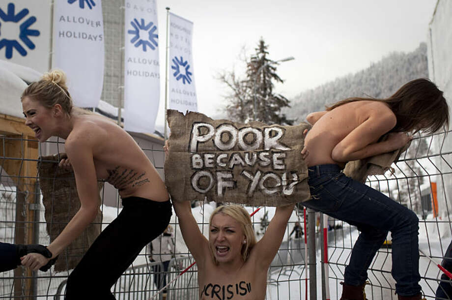 "FILE - In this Saturday, Jan. 28, 2012 file photo, topless Ukrainian protesters climb up a fence at the entrance to the congress center where the World Economic Forum takes place in Davos, Switzerland. Anja Niedringhaus, a courageous and immensely talented Associated Press photographer who has covered everything from sports to war, was killed while covering elections in Afghanistan on Friday April 4, 2014. Niedringhaus was in a car in eastern Afghanistan with AP reporter Kathy Gannon when, according to a freelancer who was with them, an Afghan policeman approached them, yelled ""Allahu Akbar"" _ God is Great _ and opened fire on them in the back seat with his AK-47. Niedringhaus was killed instantly and Gannon was wounded. (AP Photo/Anja Niedringhaus, File)"