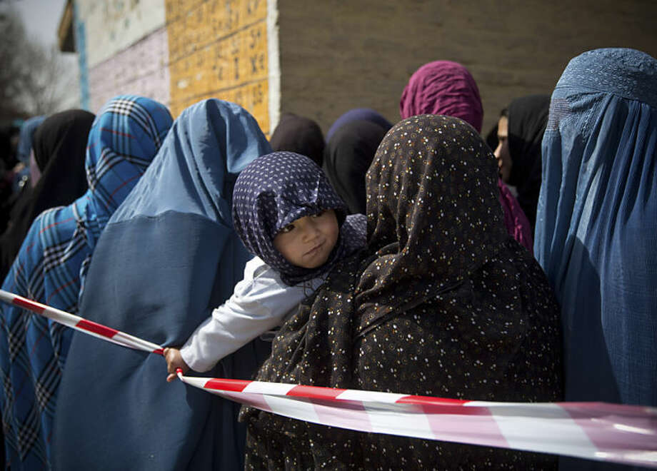 A child pulls a rope which keeps Afghan women in line queuing to get their registration card on the last day of voter registration for the upcoming presidential elections outside a school in Kabul, Afghanistan, Tuesday, April 1, 2014. Elections will take place on April 5, 2014. (AP Photo/Anja Niedringhaus)