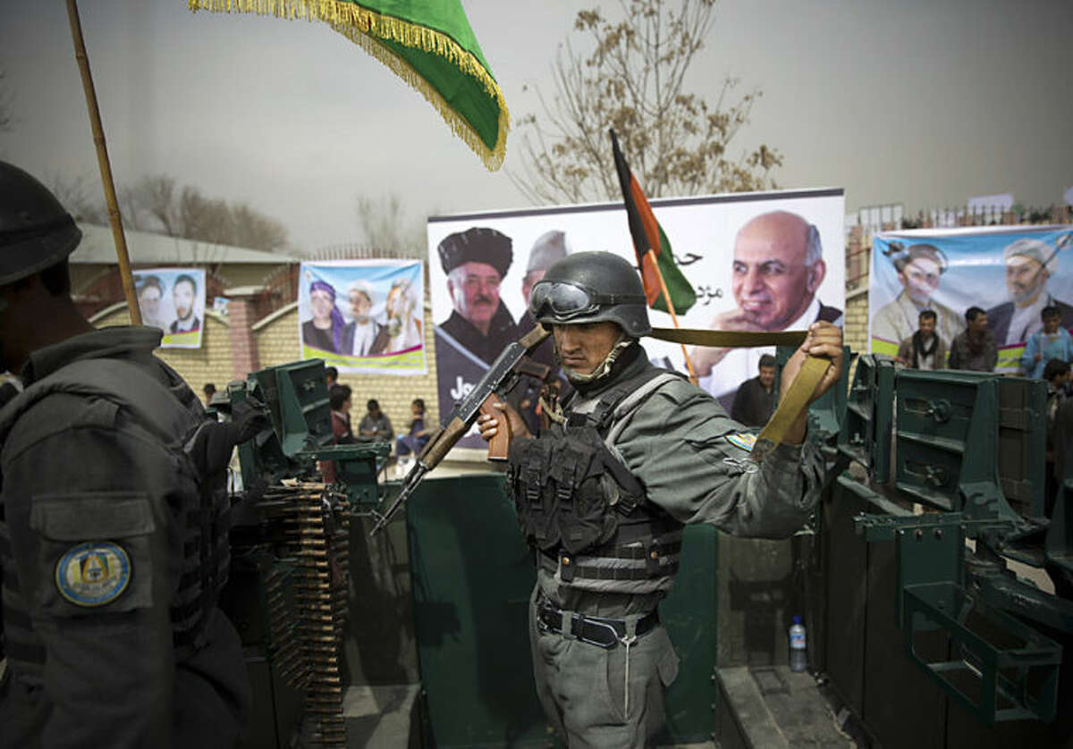 Afghan police men secure the area as Afghan presidential candidate Ashraf Ghani Ahmadza arrived for an election campaign rally to the stadium in Kabul, Afghanistan, Tuesday, April 1, 2014. Elections will take place on April 5, 2014. (AP Photo/Anja Niedringhaus)