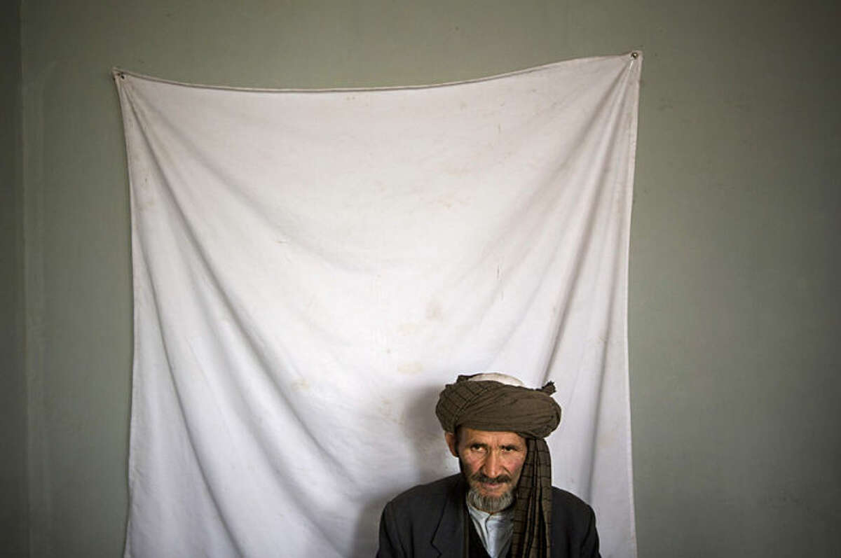 An Afghan man waits to have his picture taken for his registration card on the last day of voter registration for the upcoming presidential elections outside a school in Kabul, Afghanistan, Tuesday, April 1, 2014. Elections will take place on April 5, 2014. (AP Photo/Anja Niedringhaus)