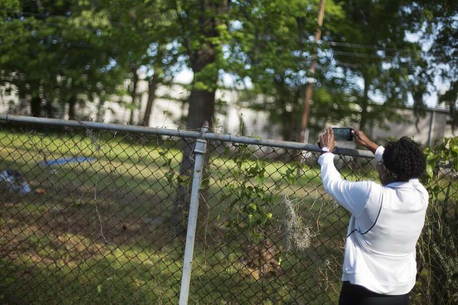 Janice Gilliard, of Summerville, S.C., takes a photo while visiting the scene where Walter Scott was killed by a North Charleston police officer Saturday after a traffic stop in North Charleston, S.C., Thursday, April 9, 2015. The officer, Michael Thomas Slager, has been fired and charged with murder. (AP Photo/David Goldman)