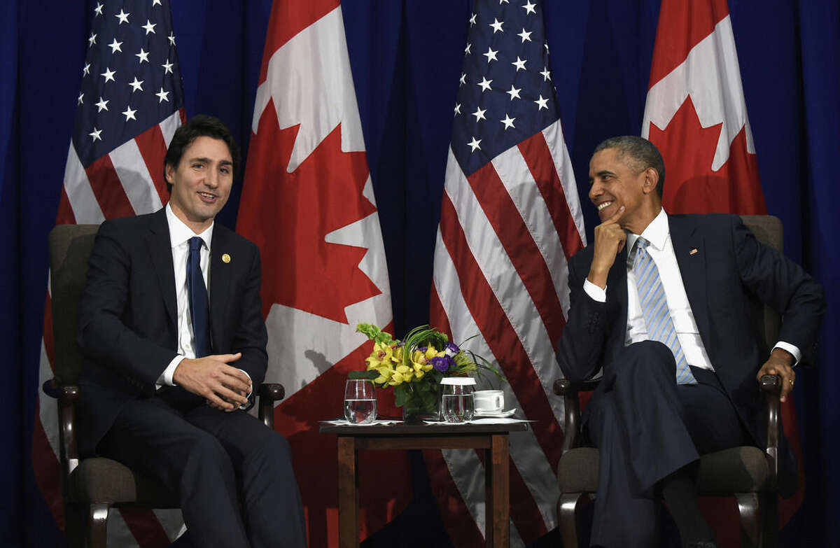 FILE - In this Nov. 19, 2015 file photo, President Barack Obama listens as Canada's Prime Minister Justin Trudeau speaks during a bilateral meeting in Manila, Philippines. Trudeau, the new, young prime minister of Canada with the movie-star looks, may pull off in just a few days what President Barack Obama has been unable to do in nearly eight years: break the fever in Washington. If only for one day. In office just a few months, Trudeau is bringing his star power to the White House later this week on his first official U.S. visit. (AP Photo/Susan Walsh, File)