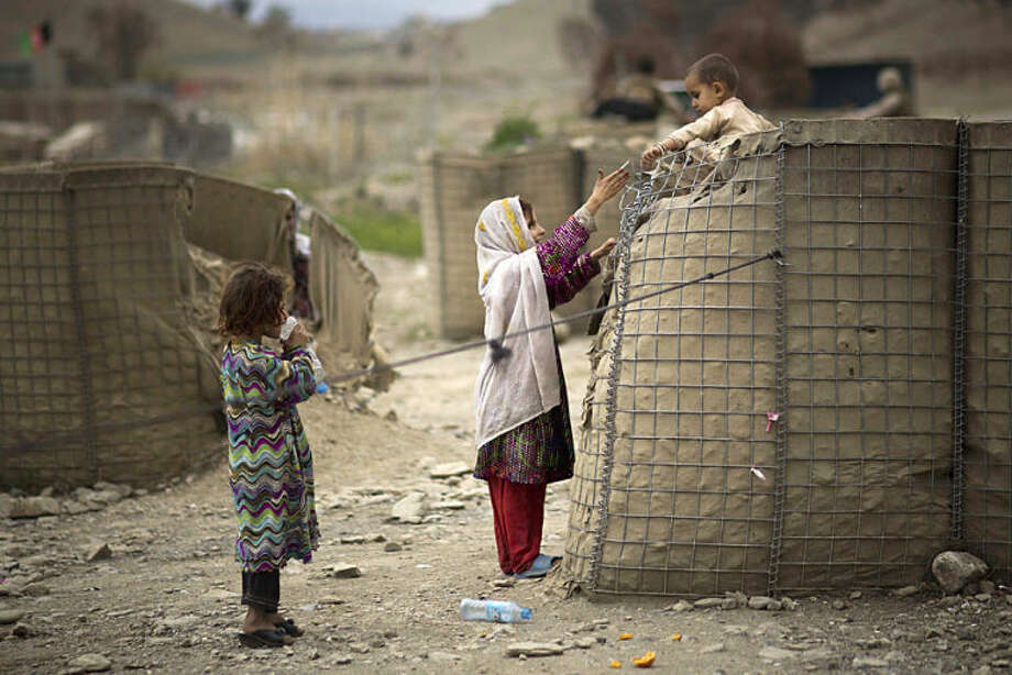 An Afghan girl helps her brother down from a security barrier set up outside the Independent Election Commission (IEC) office in the eastern Afghan city of Khost, Thursday, April 3, 2014. Afghans go to the polls to elect a new President on April 5, 2014. (AP Photo/Anja Niedringhaus)