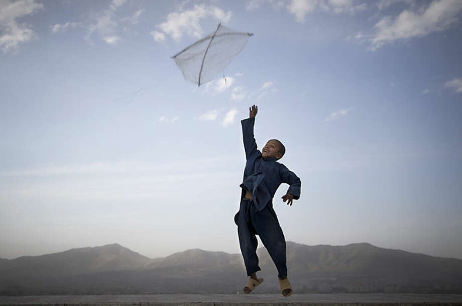 "FILE - In this May 13, 2013 file photo, an Afghan boy flies his kite on a hill overlooking Kabul, Afghanistan, May 13, 2013. Anja Niedringhaus, a courageous and immensely talented Associated Press photographer who has covered everything from sports to war, was killed while covering elections in Afghanistan on Friday April 4, 2014. Niedringhaus was in a car in eastern Afghanistan with AP reporter Kathy Gannon when, according to a freelancer who was with them, an Afghan policeman approached them, yelled ""Allahu Akbar"" _ God is Great _ and opened fire on them in the back seat with his AK-47. Niedringhaus was killed instantly and Gannon was wounded. (AP Photo/Anja Niedringhaus, File)"