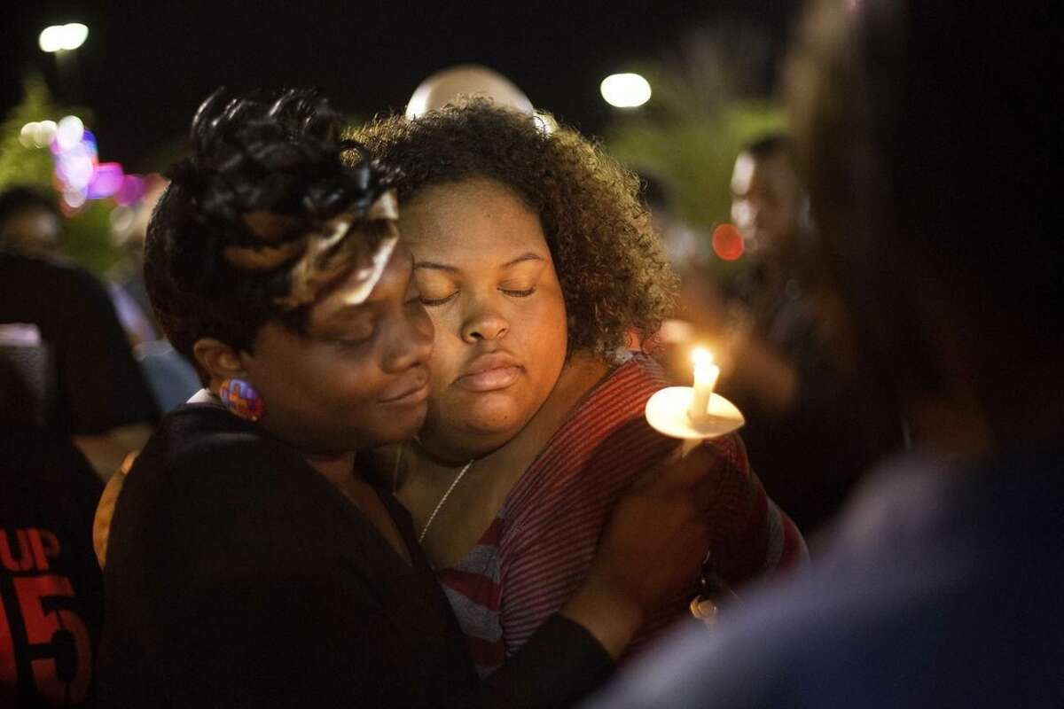 AP photo Chasyn Carter, right, of North Charleston, S.C., embraces Candice Ancrum, of Summerville, S.C., during a candlelight vigil outside city hall protesting the shooting death of Walter Lamer Scott in North Charleston, S.C.