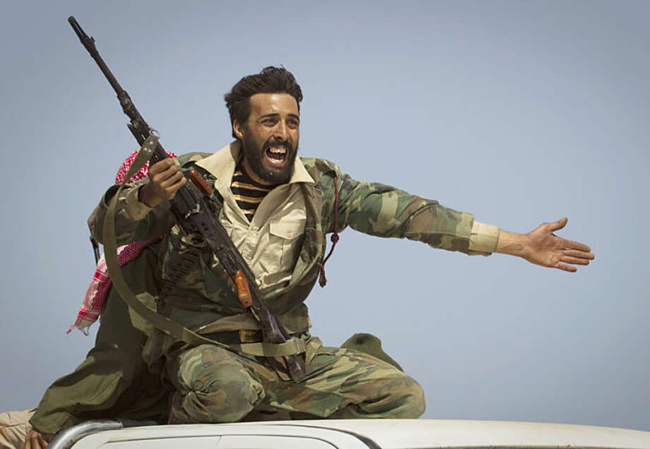 """FILE - In this March 29, 2011 file photo, a Libyan rebel urges people to leave as shelling from Gadhafi's forces started landing on the frontline outside of Bin Jawaad, 150 kilometers (93 miles) east of Sirte, central Libya. Anja Niedringhaus, a courageous and immensely talented Associated Press photographer who has covered everything from sports to war, was killed while covering elections in Afghanistan on Friday April 4, 2014. Niedringhaus was in a car in eastern Afghanistan with AP reporter Kathy Gannon when, according to a freelancer who was with them, an Afghan policeman approached them, yelled """"Allahu Akbar"""" _ God is Great _ and opened fire on them in the back seat with his AK-47. Niedringhaus was killed instantly and Gannon was wounded. (AP Photo/Anja Niedringhaus, File)"""