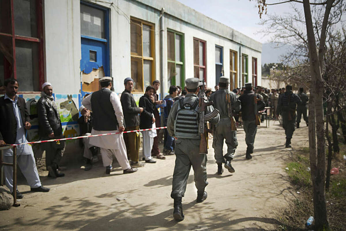 Afghan police men arrive to secure a registration center as men line up to get their registration card on the last day of voter registration for the upcoming presidential elections outside a school in Kabul, Afghanistan, Tuesday, April 1, 2014. Elections will take place on April 5, 2014. (AP Photo/Anja Niedringhaus)