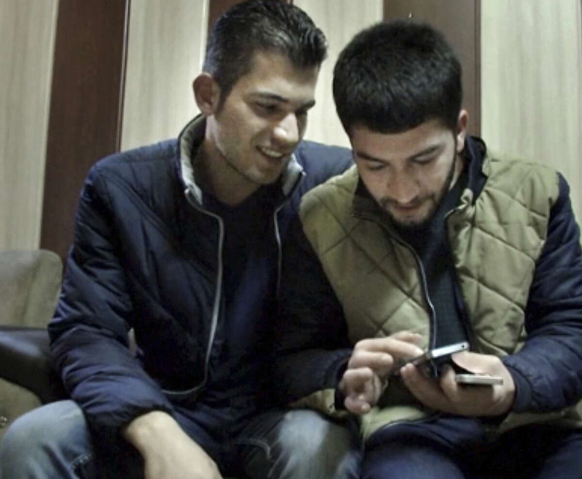 """In this Feb. 24, 2016 image made from AP video, Surkaw Omar, left, and Rebien Abdullah look at photos on a mobile phone, in Suleymaniya, Iraq. Omar and Abdullah quit their jobs and spent their life savings to migrate to Europe, only to find crowded asylum camps, hunger and freezing weather. Now back home in northern Iraq, they describe their quest for a better life as a disaster. """"When we arrived there, it was winter. It was freezing. They put me in a room with three Syrians. I couldn't speak Arabic and they couldn't speak Kurdish. We were communicating like deaf people,"""" Omar said. After trying Germany one more time, they gave up. """"We said to each other, let's go home. It's better than anywhere else,"""" he said. (AP Photo/Balint Szlanko)"""
