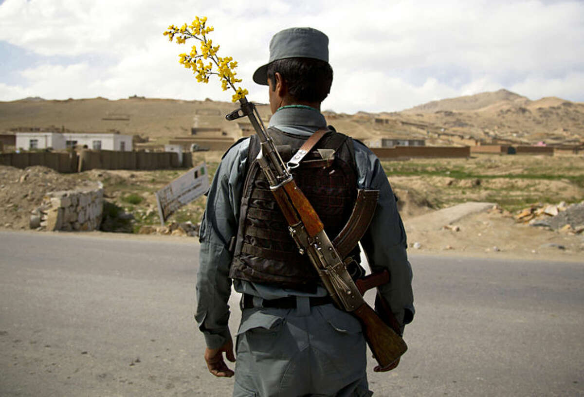 """FILE - In this Wednesday, May 15, 2013 file photo, an Afghan National Police officer mans a checkpoint in the outskirts of Maidan Shahr, Wardak province, Afghanistan. Anja Niedringhaus, a courageous and immensely talented Associated Press photographer who has covered everything from sports to war, was killed while covering elections in Afghanistan on Friday April 4, 2014. Niedringhaus was in a car in eastern Afghanistan with AP reporter Kathy Gannon when, according to a freelancer who was with them, an Afghan policeman approached them, yelled """"Allahu Akbar"""" - God is Great -and opened fire on them in the back seat with his AK-47. Niedringhaus was killed instantly and Gannon was wounded. (AP Photo/Anja Niedringhaus, File)"""