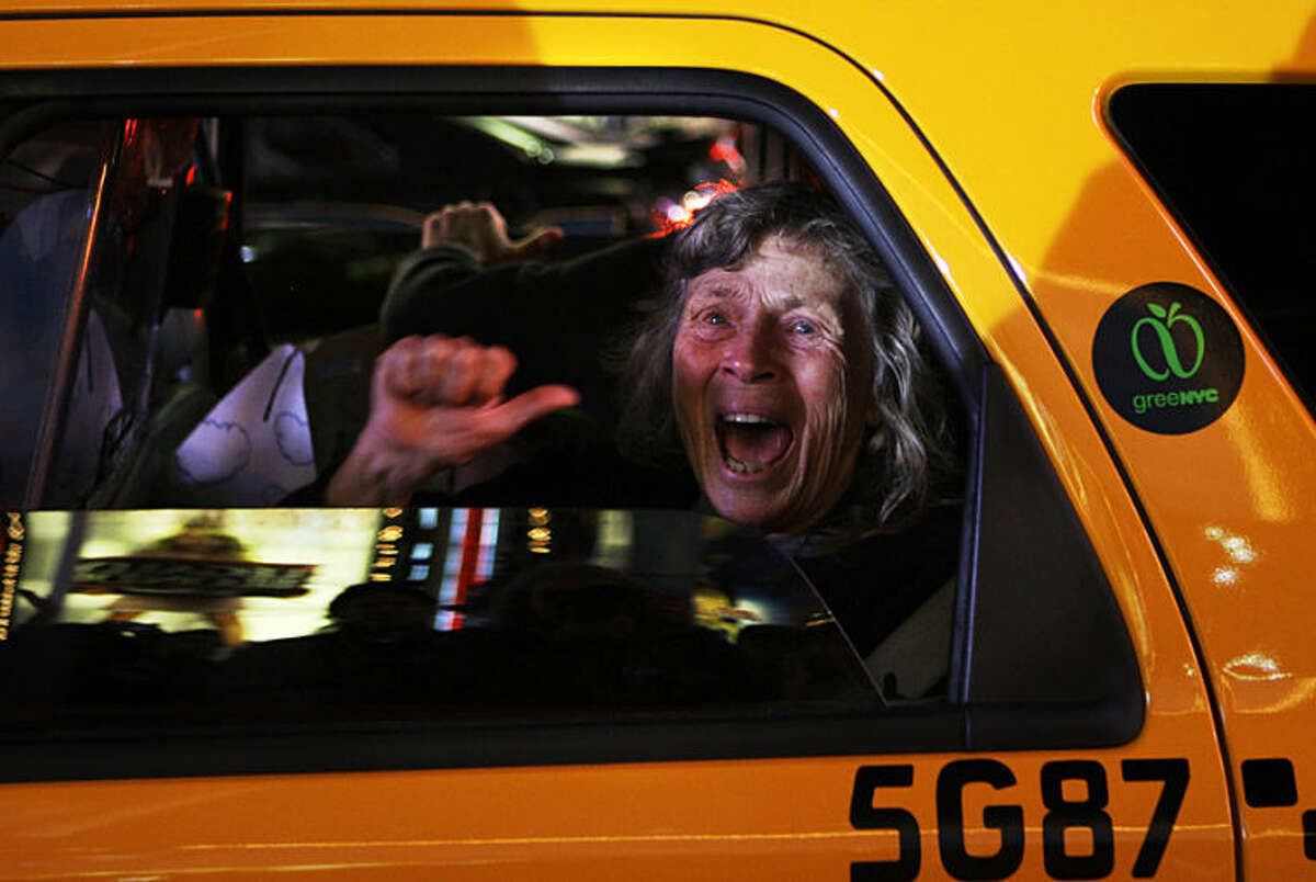 """FILE - In this Tuesday, Nov. 4, 2008 file photo, a woman reacts while sitting in a New York taxi as different television networks call the presidential race for Barack Obama, in New York. Anja Niedringhaus, a courageous and immensely talented Associated Press photographer who has covered everything from sports to war, was killed while covering elections in Afghanistan on Friday April 4, 2014. Niedringhaus was in a car in eastern Afghanistan with AP reporter Kathy Gannon when, according to a freelancer who was with them, an Afghan policeman approached them, yelled """"Allahu Akbar"""" - God is Great -and opened fire on them in the back seat with his AK-47. Niedringhaus was killed instantly and Gannon was wounded. (AP Photo/Anja Niedringhaus, File)"""