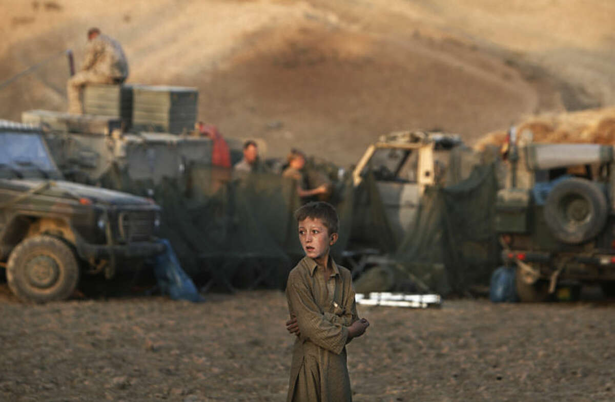 """FILE - In this Monday, Sept. 14, 2009 file photo, an Afghan boy looks on as German ISAF soldiers prepare a temporary camp to overnight during a long term patrol in the mountainous region of Feyzabad, east of Kunduz, Afghanistan. Anja Niedringhaus, a courageous and immensely talented Associated Press photographer who has covered everything from sports to war, was killed while covering elections in Afghanistan on Friday April 4, 2014. Niedringhaus was in a car in eastern Afghanistan with AP reporter Kathy Gannon when, according to a freelancer who was with them, an Afghan policeman approached them, yelled """"Allahu Akbar"""" _ God is Great _ and opened fire on them in the back seat with his AK-47. Niedringhaus was killed instantly and Gannon was wounded. (AP Photo/Anja Niedringhaus, File)"""