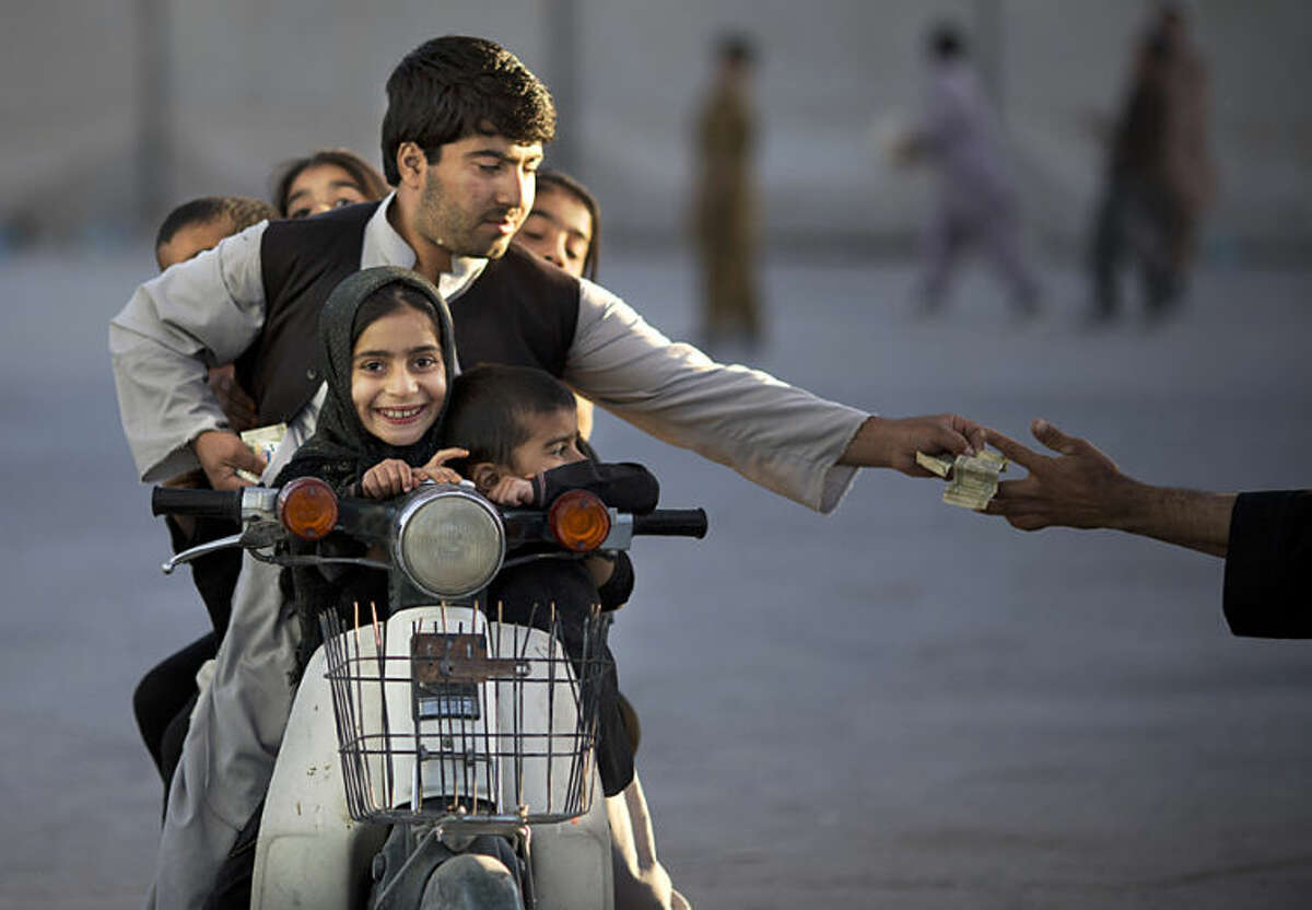"""FILE - In this Friday, Nov. 1, 2013 file photo, an Afghan man with his five children on his motorbike pays money to enter a park in Kandahar, southern Afghanistan. Anja Niedringhaus, a courageous and immensely talented Associated Press photographer who has covered everything from sports to war, was killed while covering elections in Afghanistan on Friday April 4, 2014. Niedringhaus was in a car in eastern Afghanistan with AP reporter Kathy Gannon when, according to a freelancer who was with them, an Afghan policeman approached them, yelled """"Allahu Akbar"""" - God is Great -and opened fire on them in the back seat with his AK-47. Niedringhaus was killed instantly and Gannon was wounded. (AP Photo/Anja Niedringhaus, File)"""