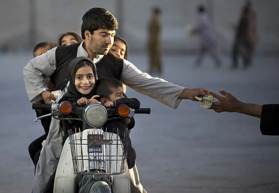 "FILE - In this Friday, Nov. 1, 2013 file photo, an Afghan man with his five children on his motorbike pays money to enter a park in Kandahar, southern Afghanistan. Anja Niedringhaus, a courageous and immensely talented Associated Press photographer who has covered everything from sports to war, was killed while covering elections in Afghanistan on Friday April 4, 2014. Niedringhaus was in a car in eastern Afghanistan with AP reporter Kathy Gannon when, according to a freelancer who was with them, an Afghan policeman approached them, yelled ""Allahu Akbar"" - God is Great -and opened fire on them in the back seat with his AK-47. Niedringhaus was killed instantly and Gannon was wounded. (AP Photo/Anja Niedringhaus, File)"