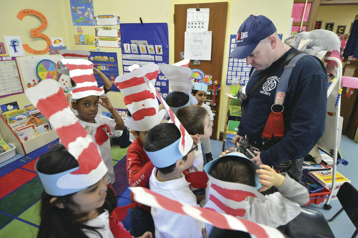 """Hour photos/Alex von Kleydorff Norwalk Firefighter Mike Delaney answers some questions from Tracey Elementary School students after reading Dr. Seuss' """"The Foot Book"""" on Dr. Seuss Day Wednesday."""