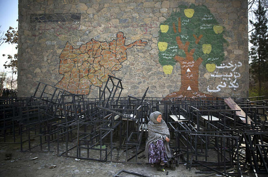 An Afghan woman sits on destroyed school benches as she waits to get her registration card on the last day of voter registration for the upcoming presidential elections outside a school in Kabul, Afghanistan, Tuesday, April 1, 2014. Elections will take place on April 5, 2014. (AP Photo/Anja Niedringhaus)