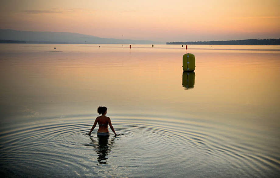 """FILE - In this Sunday, July 21, 2013 file photo, a woman takes a dip in Lake Geneva at sunrise in Geneva, Switzerland. Anja Niedringhaus, a courageous and immensely talented Associated Press photographer who has covered everything from sports to war, was killed while covering elections in Afghanistan on Friday April 4, 2014. Niedringhaus was in a car in eastern Afghanistan with AP reporter Kathy Gannon when, according to a freelancer who was with them, an Afghan policeman approached them, yelled """"Allahu Akbar"""" _ God is Great _ and opened fire on them in the back seat with his AK-47. Niedringhaus was killed instantly and Gannon was wounded. (AP Photo/Anja Niedringhaus, File)"""