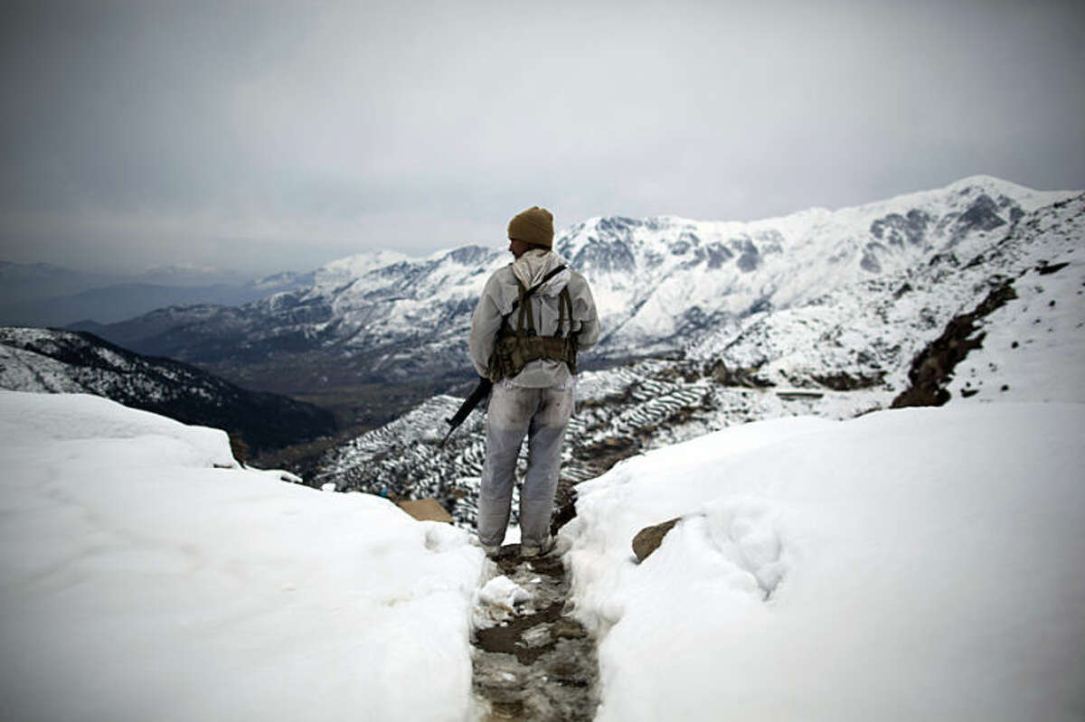 """FILE - In this Friday, Feb. 17, 2012 file photo, a Pakistani Army soldier with the 20th Lancers Armored Regiment stands atop the 8000-foot mountain during a patrol near his outpost, Kalpani Base, in Pakistan's Dir province on the Pakistan-Afghan border. Anja Niedringhaus, a courageous and immensely talented Associated Press photographer who has covered everything from sports to war, was killed while covering elections in Afghanistan on Friday April 4, 2014. Niedringhaus was in a car in eastern Afghanistan with AP reporter Kathy Gannon when, according to a freelancer who was with them, an Afghan policeman approached them, yelled """"Allahu Akbar"""" _ God is Great _ and opened fire on them in the back seat with his AK-47. Niedringhaus was killed instantly and Gannon was wounded. (AP Photo/Anja Niedringhaus, File)"""
