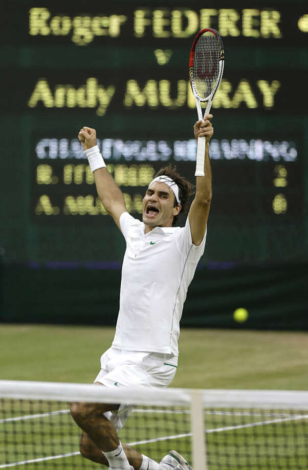 "FILE - In this Sunday, July 8, 2012 file photo, Roger Federer of Switzerland celebrates winning the men's singles final against Andy Murray of Britain at the All England Lawn Tennis Championships at Wimbledon, England. Anja Niedringhaus, a courageous and immensely talented Associated Press photographer who has covered everything from sports to war, was killed while covering elections in Afghanistan on Friday April 4, 2014. Niedringhaus was in a car in eastern Afghanistan with AP reporter Kathy Gannon when, according to a freelancer who was with them, an Afghan policeman approached them, yelled ""Allahu Akbar"" _ God is Great _ and opened fire on them in the back seat with his AK-47. Niedringhaus was killed instantly and Gannon was wounded. (AP Photo/Anja Niedringhaus, File)"