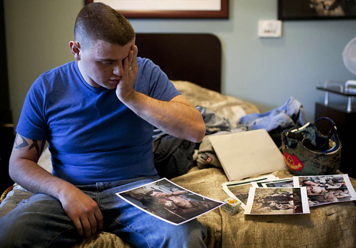 """FILE - In this Tuesday, Dec. 13, 2011 file photo, injured United States Marine Cpl. Burness Britt reacts after seeing pictures of his evacuation laid out on his bed in the Hunter Holmes Medical Center in Richmond, Va. Anja Niedringhaus, a courageous and immensely talented Associated Press photographer who has covered everything from sports to war, was killed while covering elections in Afghanistan on Friday April 4, 2014. Niedringhaus was in a car in eastern Afghanistan with AP reporter Kathy Gannon when, according to a freelancer who was with them, an Afghan policeman approached them, yelled """"Allahu Akbar"""" _ God is Great _ and opened fire on them in the back seat with his AK-47. Niedringhaus was killed instantly and Gannon was wounded. (AP Photo/Anja Niedringhaus, File)"""