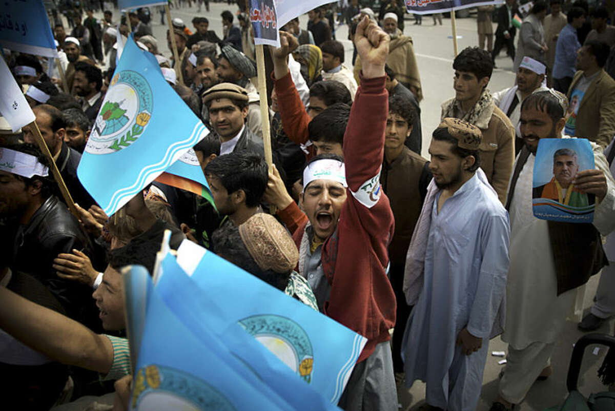 An Afghan man shouts in support for presidential candidate Ashraf Ghani Ahmadza as he arrives with others for an election campaign rally to the stadium in Kabul, Afghanistan, Tuesday, April 1, 2014. Elections will take place on April 5, 2014. (AP Photo/Anja Niedringhaus)