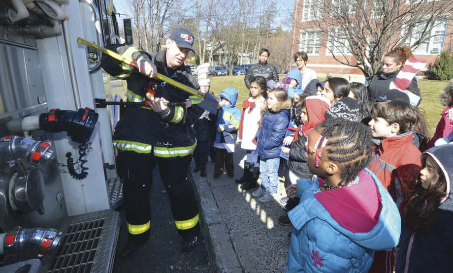 Hour Photo/Alex von Kleydorff Norwalk Firefighter Brian Kilcoyne shows some of the Kindergarten class at Tracey school what they use to fight fires during a visit to the school on Dr. Seuss Day