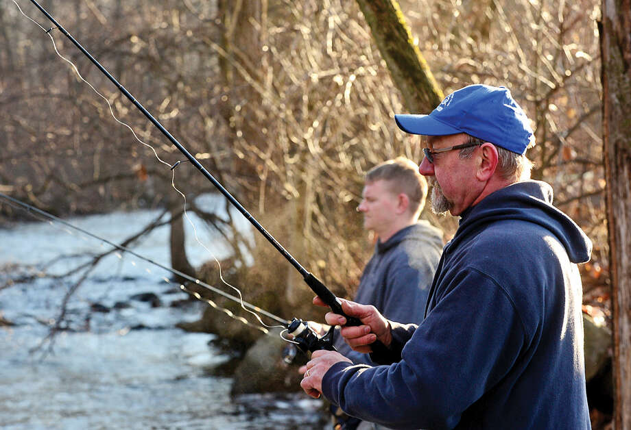 Hour photo / Erik Trautmann Local resident including Pete Delinski and his son Kevin fish for trout on the Norwalk River in Wilton on Opening Day Saturday.