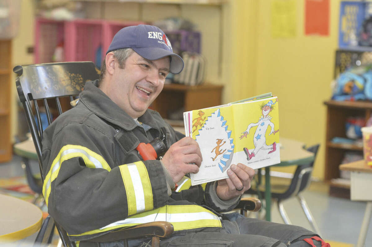 Hour Photo/Alex von Kleydorff Norwalk Fire department's Lt. Chris Riccio reads Fox in Sox to a Kindergarten class at Tracey school on Dr. Seuss day