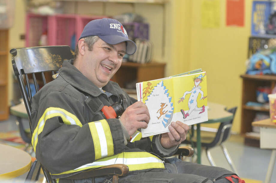 Hour Photo/Alex von Kleydorff Norwalk Fire department's Lt. Chris Riccio reads Fox in Sox to a Kindergarten class at Tracey school on Dr. Seuss day