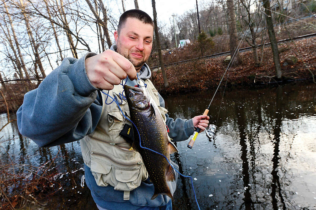 Hour photo / Erik Trautmann Local resident including Kevin Botelho fish for trout on the Norwalk River in Wilton on Opening Day Saturday.