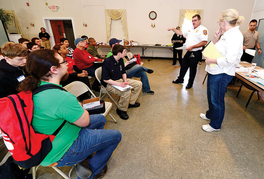 Hour photo / Erik Trautmann Norwalk Fire Department Fire Marshal Chris Hansen and American Red Cross senior director of community preparedness, Stacey Hafen, coordinate a fire safety campaign Saturday where teams made up of City Fire department staff, Public Safety cadets, and Red Cross volunteers train to go door-to-door in the South Norwalk area to install new smoke detectors in homes and perform home fire safety checks.