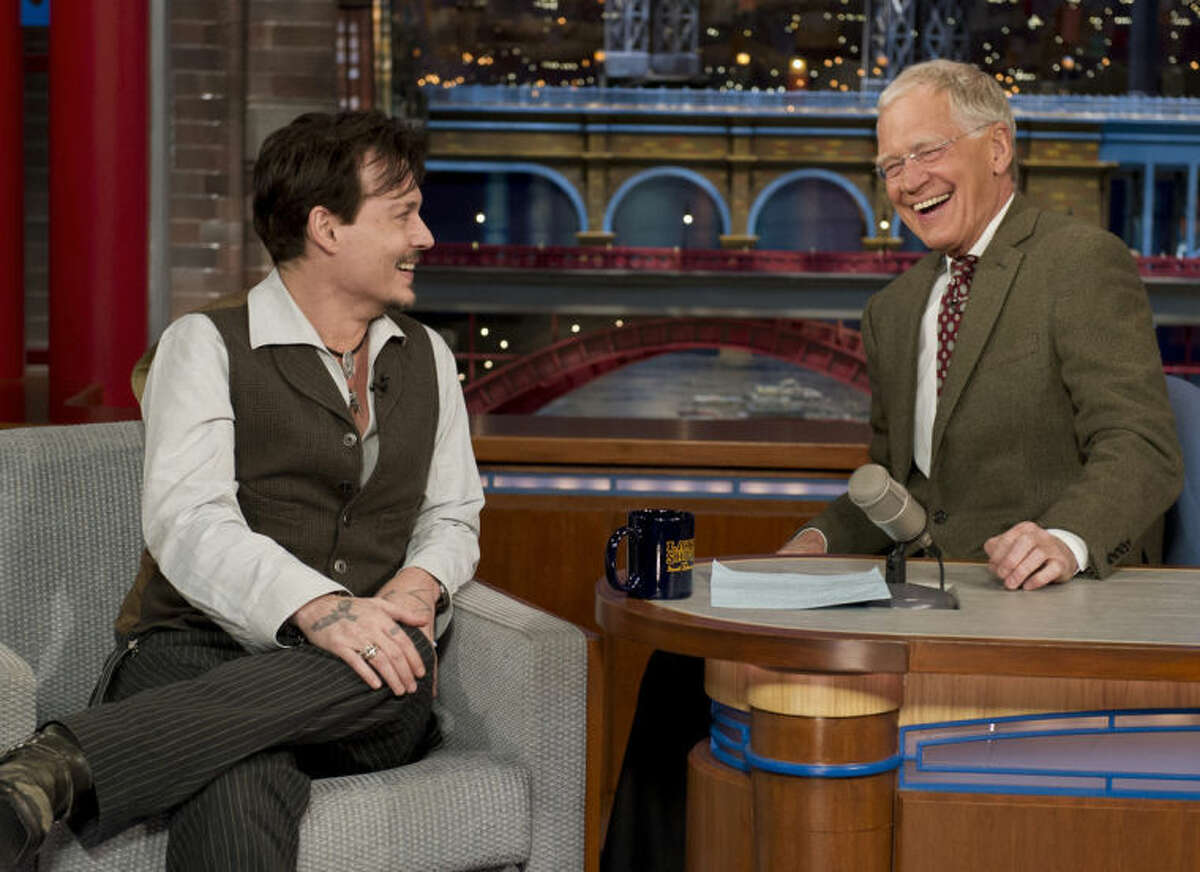 """In this photo provided by CBS, actor Johnny Depp, left, joins host David Letterman on the set of the ?""""Late Show with David Letterman,?"""" Thursday, April 3, 2014, in New York. Earlier during Thursday?'s taping, Letterman informed the audience that he will retire in 2015, at the end of his current contract. Letterman steps down with the longest tenure of any late-night talk show host in U.S. television history. (AP Photo/CBS, Jeffrey R. Staab) MANDATORY CREDIT, NO SALES, NO ARCHIVE, FOR NORTH AMERICAN USE ONLY"""