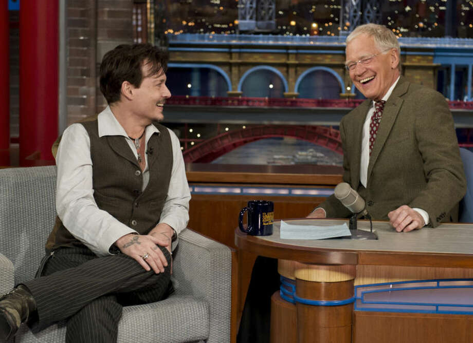 "In this photo provided by CBS, actor Johnny Depp, left, joins host David Letterman on the set of the ""Late Show with David Letterman,"" Thursday, April 3, 2014, in New York. Earlier during Thursday's taping, Letterman informed the audience that he will retire in 2015, at the end of his current contract. Letterman steps down with the longest tenure of any late-night talk show host in U.S. television history. (AP Photo/CBS, Jeffrey R. Staab) MANDATORY CREDIT, NO SALES, NO ARCHIVE, FOR NORTH AMERICAN USE ONLY"