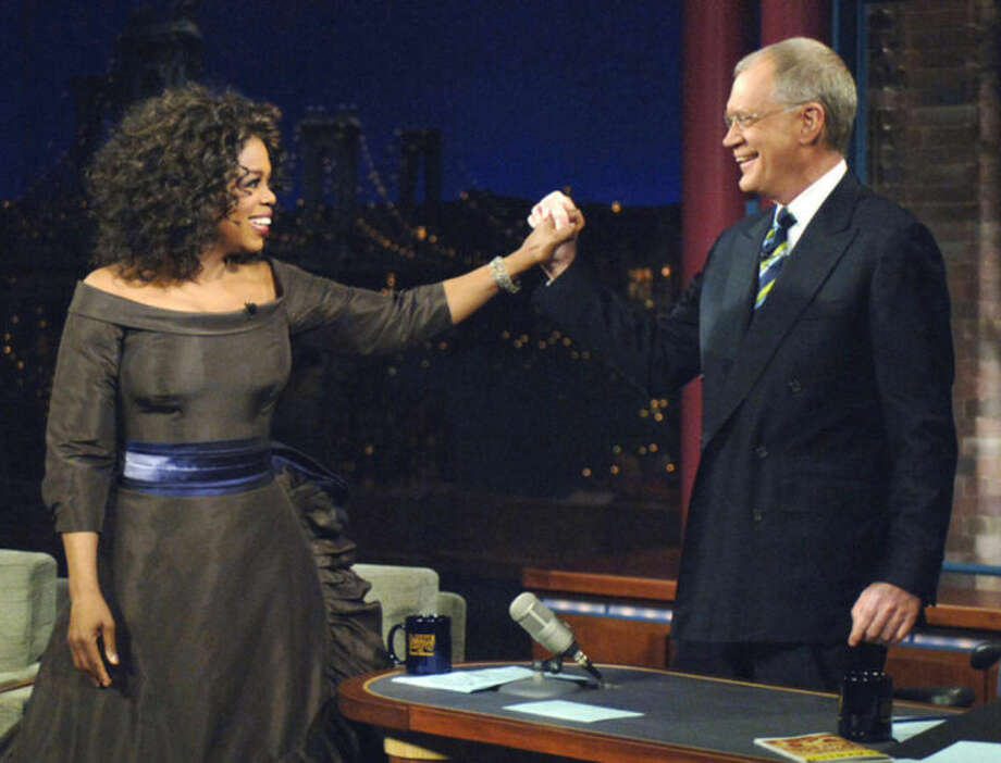 """FILE - In this Dec. 1, 2005 file photo provided by CBS, Oprah Winfrey appears with David Letterman during a taping of on """"The Late Show with David Letterman"""", in New York. Following the interview, Dave escorted Oprah across 53rd street to the opening of her new Broadway Show """"The Color Purple"""". Letterman announced his retirement during a taping on Thursday, April 3, 2014. Although no specific date was announced he told the audience that he will leave his desk sometime in 2015. (AP Photo/Jeffrey R. Staab/CBS)"""