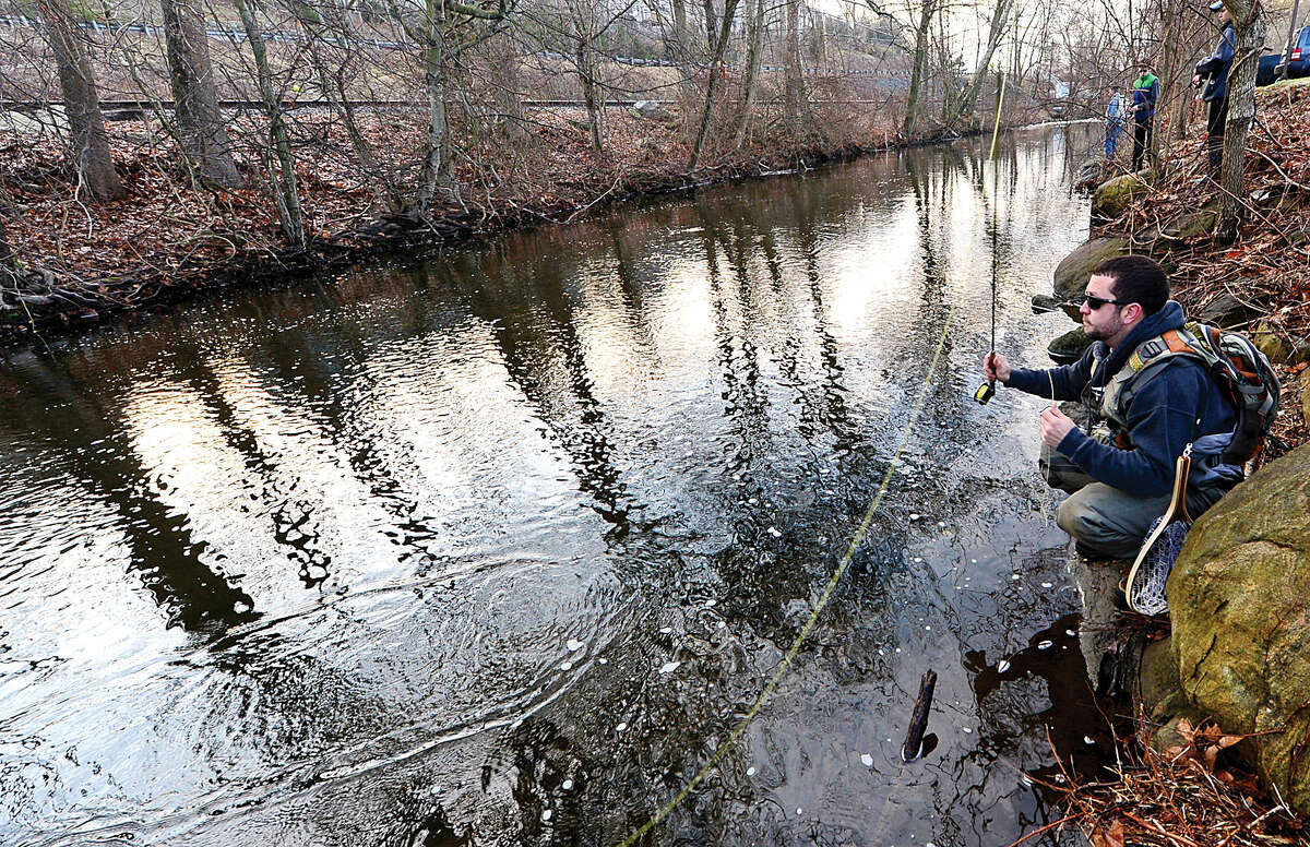 Hour photo / Erik Trautmann Local resident including Tom Lametta fish for trout on the Norwalk River in Wilton on Opening Day Saturday.