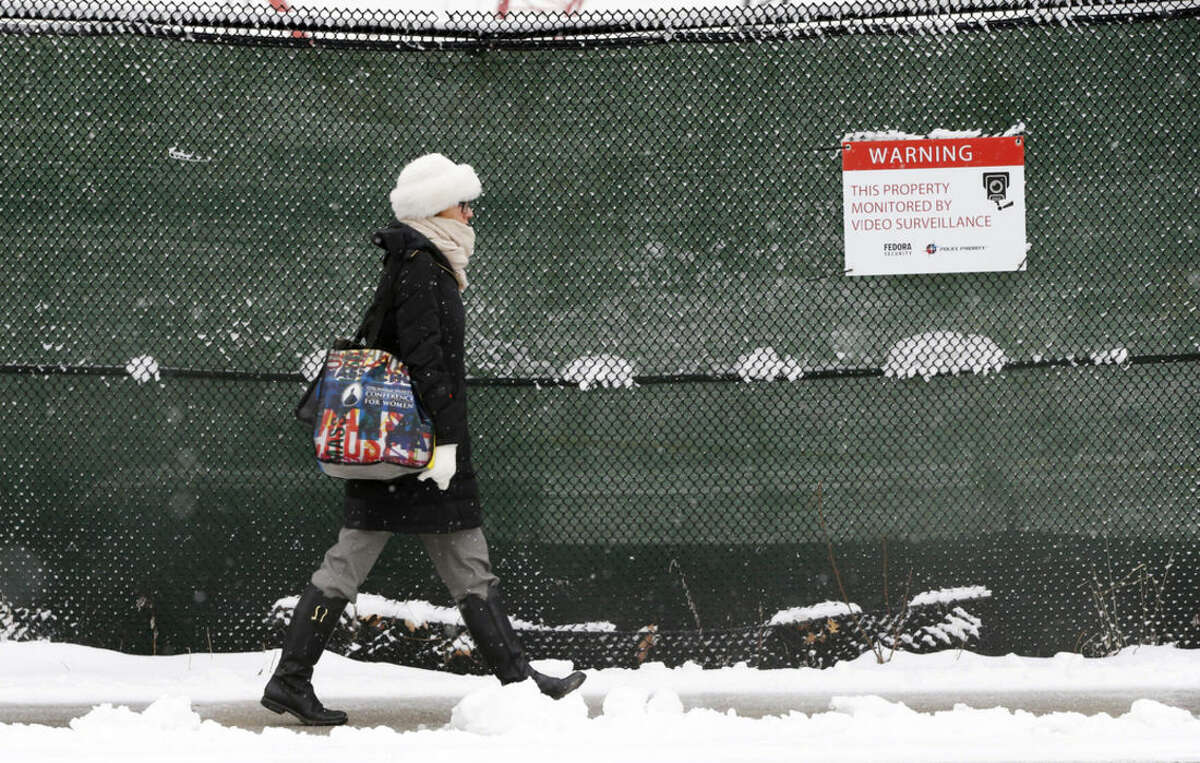 A woman walks past a construction site as snow falls in the East Boston neighborhood of Boston, Monday, March 21, 2016. The National Weather Service says southeastern Massachusetts, including Boston and Rhode Island could get several inches of snow through Monday morning. (AP Photo/Michael Dwyer)