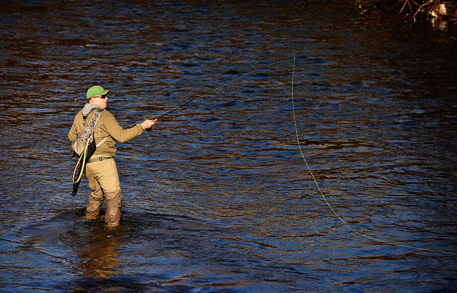 Hour photo / Erik Trautmann Local resident including Ben Couch fish for trout on the Norwalk River in Wilton on Opening Day Saturday.