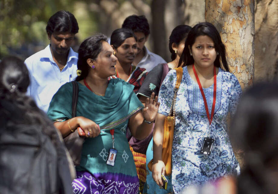 In this Wednesday, March 26, 2014 photo, young Indian employees of Infosys Technologies walk outside the company's headquarters at Electronic City in Bangalore, India. As the world's largest democracy of 1.2 billion people, including 814 million voters, launches a marathon six-week national election contest, all eyes are on India's enormous population of ambitious, tech-savvy and politically engaged youths. Nowhere is the high-tech transition more clear than amid the bright cafes and technology companies of Bangalore, seen as the economy's beating heart and brain trust with its large number of scientists, engineers and corporate professionals drawn from India's brightest youths. With 63 percent of its population under 25, Bangalore is one of India's youngest cities. (AP Photo/Kashif Masood)