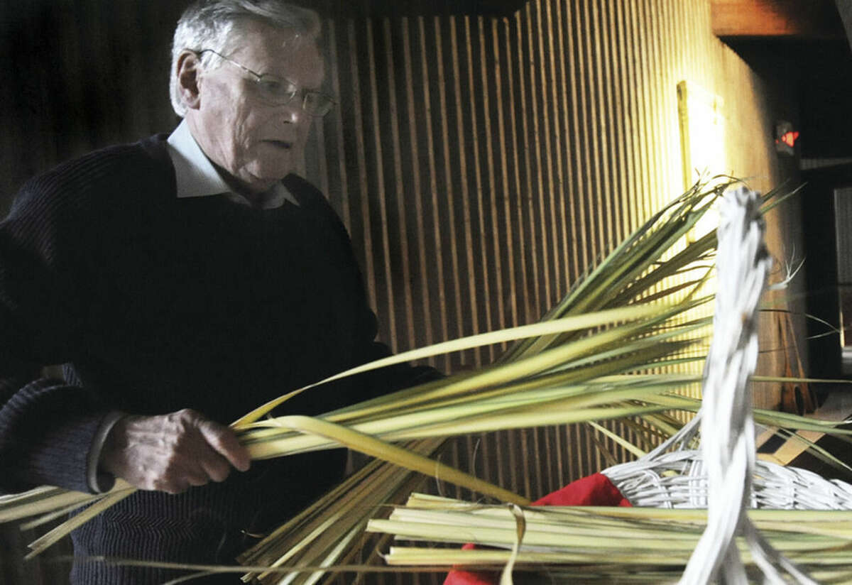 Hour photos/Matthew Vinci Above, Jerry Meehan lays out palms at the Palm Sunday service at St. Phillip Church in Norwalk. Below, Mary Bauer leads a hymn during the Palm Sunday service.