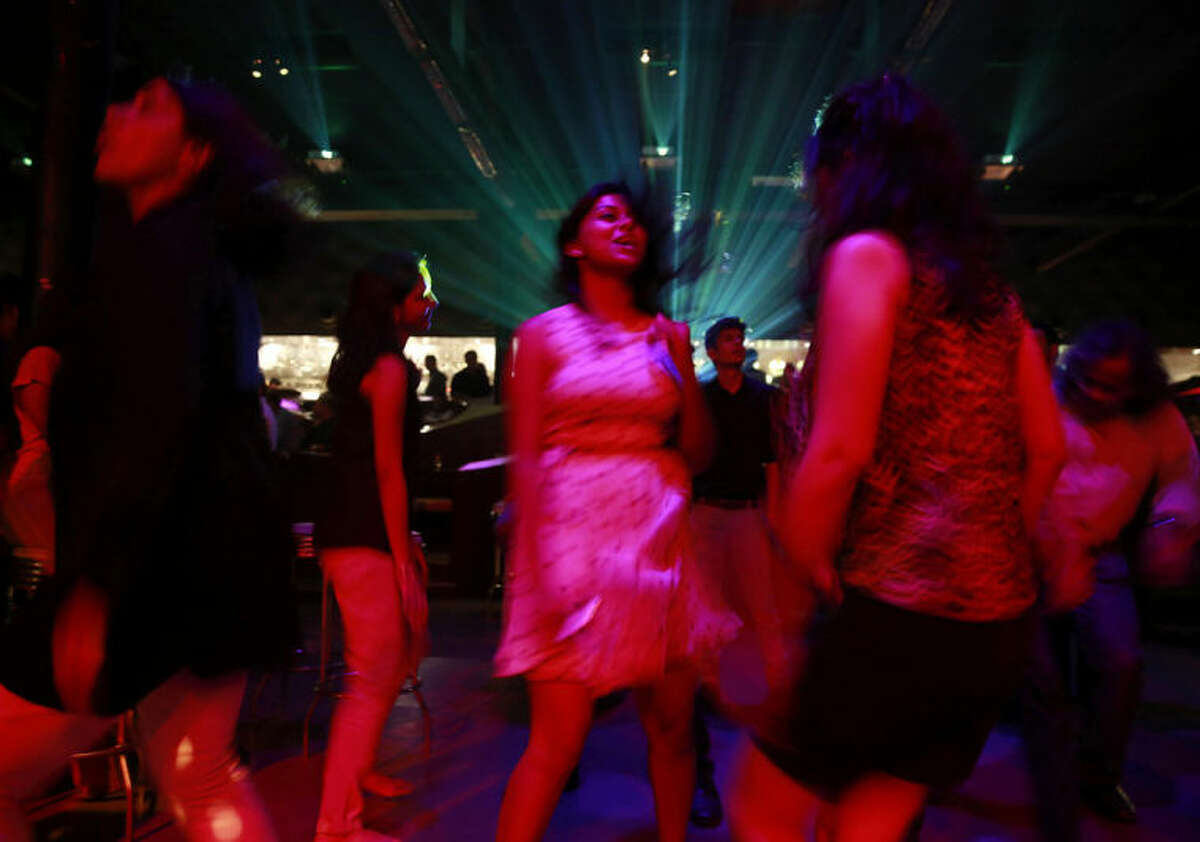"""In this Wednesday, April 2, 2014 photo, young Indian women dance at a night club """"blueFROG"""" in Mumbai, India. As India begins its weekslong election process Monday, April 7, the enormous population of ambitious, tech-savvy and politically engaged youths has more potential than ever to sway the outcome. More than 378 million of India?'s 814 million eligible voters between 18 and 35, according to census records. (AP Photo/Rafiq Maqbool)"""