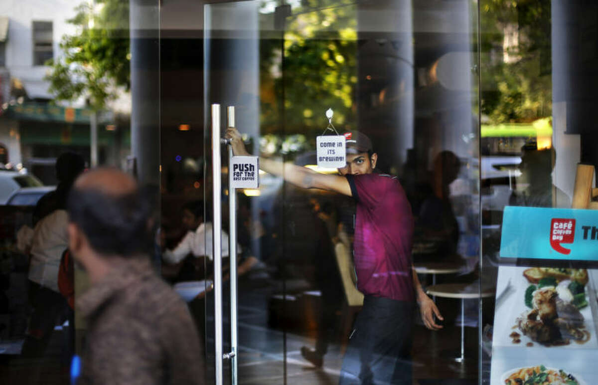 In this Monday, March 31, 2014 photo, an Indian waiter stands at the entrance of a cafe at a shopping center in New Delhi, India. As India begins its weekslong election process Monday, April 7, the enormous population of ambitious, tech-savvy and politically engaged youths has more potential than ever to sway the outcome. More than 378 million of India?'s 814 million eligible voters between 18 and 35, according to census records. (AP Photo/Altaf Qadri)