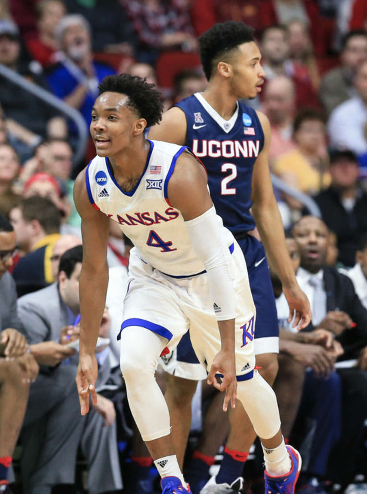 Kansas' Devonte' Graham (4) celebrates a three point shot as he runs past Connecticut's Jalen Adams (2) during a second-round men's college basketball game in the NCAA Tournament in Des Moines, Iowa, Saturday, March 19, 2016. (AP Photo/Nati Harnik)
