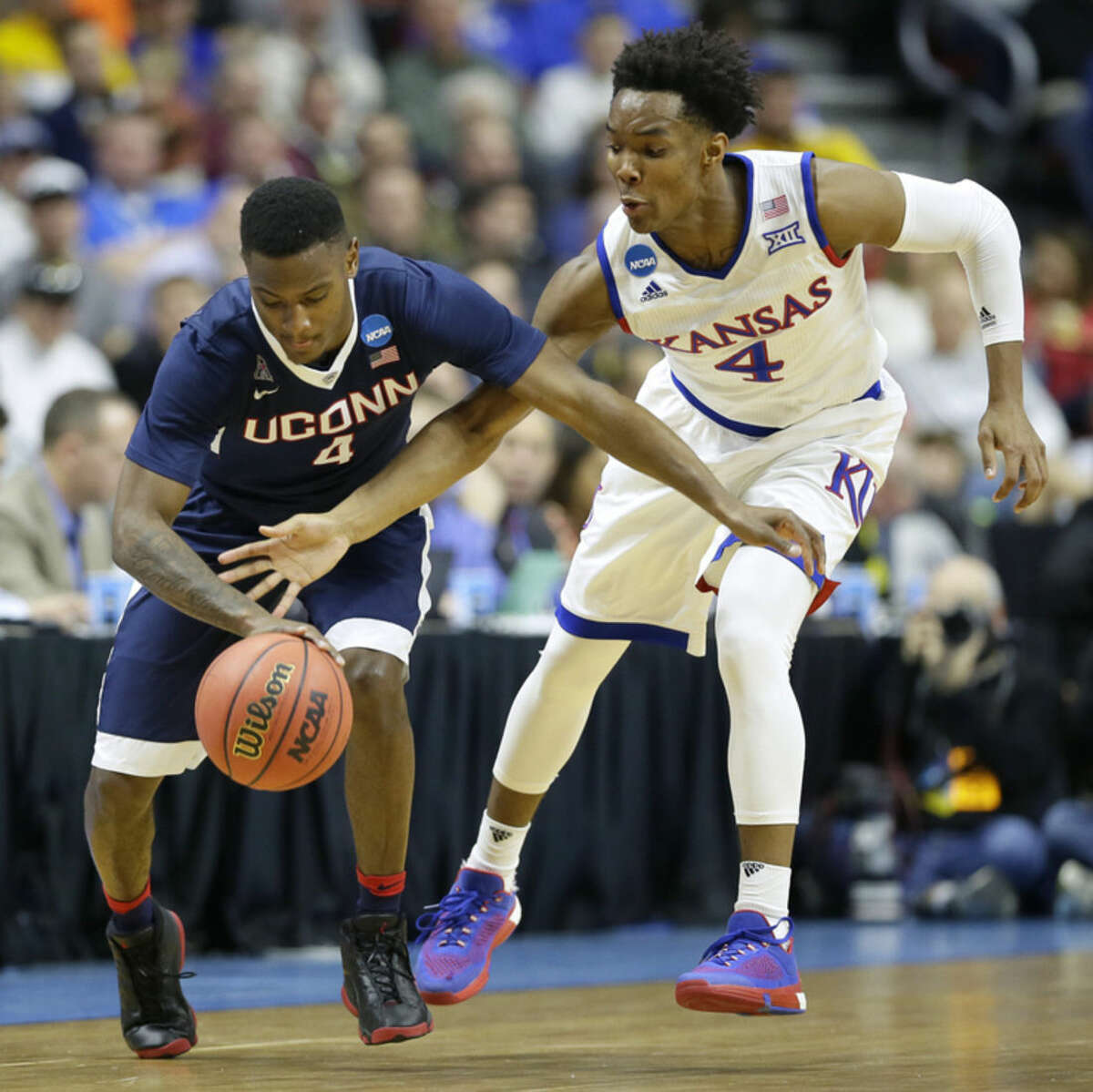 Kansas guard Devonte' Graham, right, tries to steal the ball from Connecticut guard Sterling Gibbs during the first half of a second-round men's college basketball game in the NCAA Tournament, Saturday, March 19, 2016, in Des Moines, Iowa. (AP Photo/Charlie Neibergall)