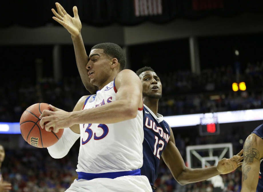Kansas forward Landen Lucas drives past Connecticut forward Kentan Facey, right, during the first half of a second-round men's college basketball game in the NCAA Tournament, Saturday, March 19, 2016, in Des Moines, Iowa. (AP Photo/Charlie Neibergall)