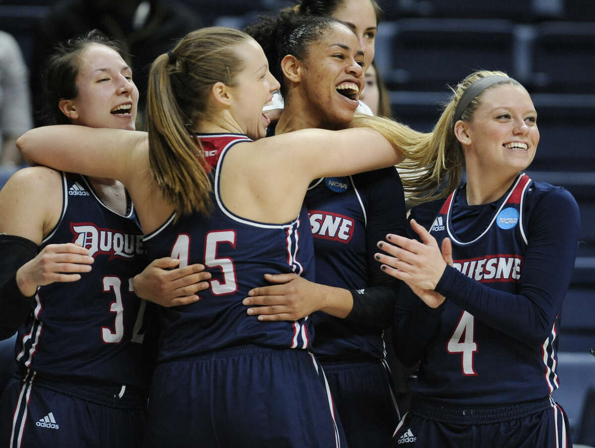 Duquesne's April Robinson, Emilie Gronas, Deva'Nyar Workman, and Chassidy Omogrosso, from the left, celebrate in the final seconds of a first round women's college basketball game against Seton Hall in the NCAA Tournament, Saturday, March 19, 2016, in Storrs, Conn. Duquesne won 97-76. (AP Photo/Jessica Hill)