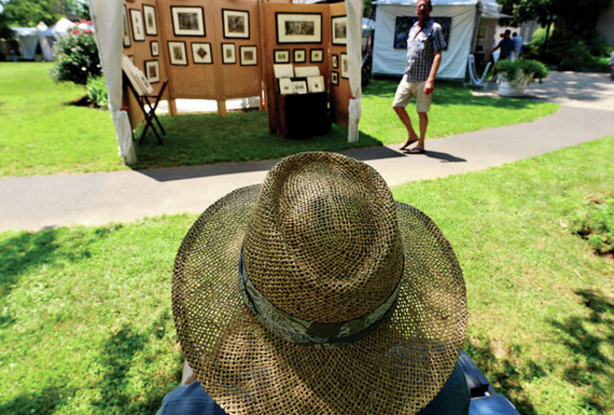 Grant Silverstein looks over his kiosk of etchings during the first annual Norwalk Art Festival at Mathews Park Saturday. Hour photo / Erik Trautmann