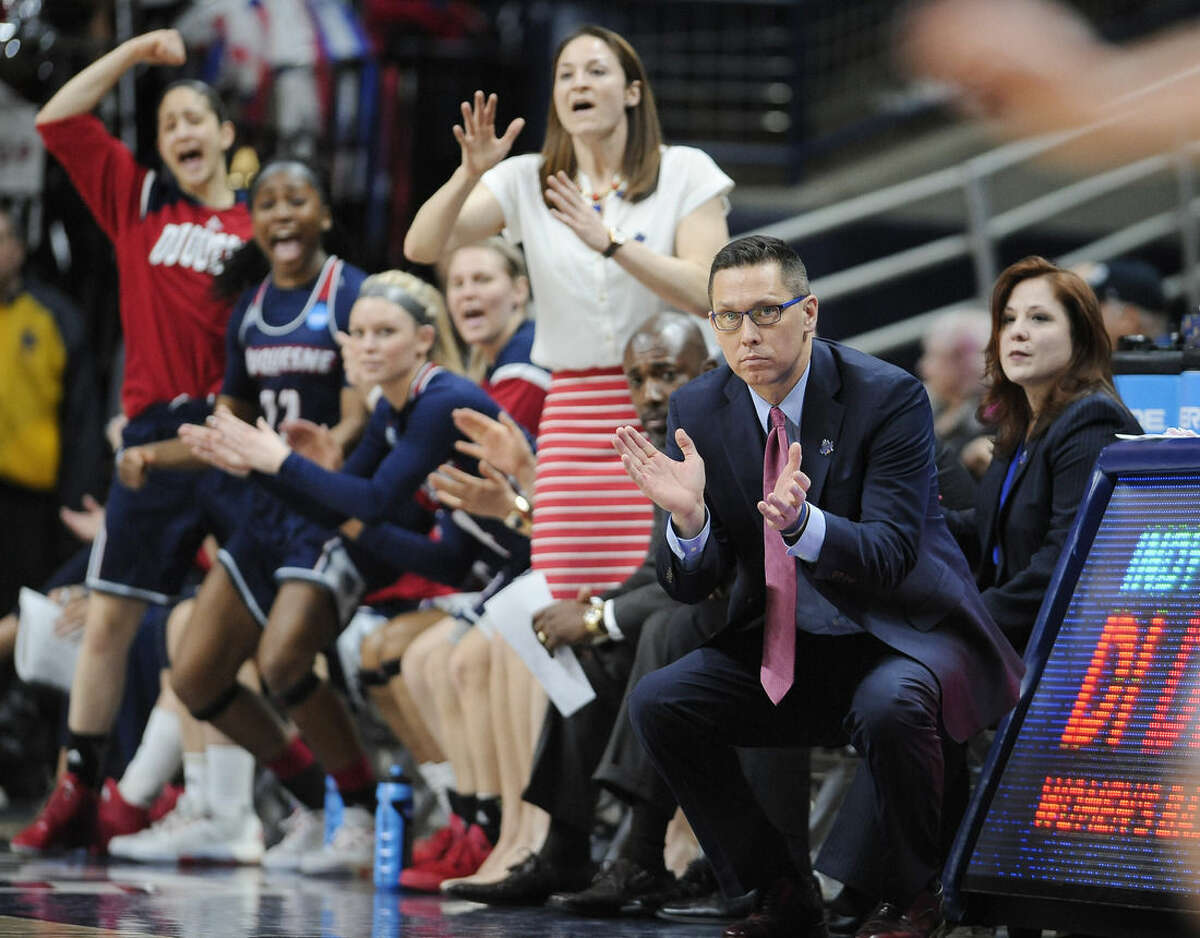 Duquesne head coach Dan Burt, right, watches play with his team during the first half of a first-round women's college basketball game against Seton Hall in the NCAA Tournament, Saturday, March 19, 2016, in Storrs, Conn. Duquesne won 97-76. (AP Photo/Jessica Hill)