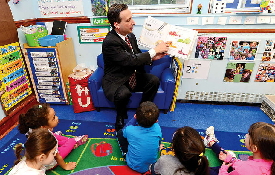 "Hour photo / Erik Trautmann In celebration of the Week of the Young Child State Senate Majority Leader Bob Duff was a guest at Carousel Preschool where he read ""Dragons Love Tacos"" to 4-year-old students Tuesday."